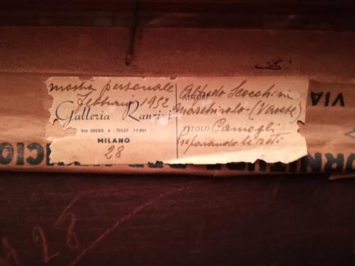 Cartiglio situato  in alto sul retro della cornice sul quale sono riportate descrizioni sul quadro tra cui il titolo e la firma dell'autore.