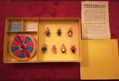 """Confezione con i 7 personaggi di """"Fortunello"""" , la ruota della fortuna di legno , 12 carte a mazzetto delle carte """"Attenzione , Attenzione"""" e """"Scherzi della vita"""" , 1 plancia di gioco e il libretto delle regole e del contenuto ."""