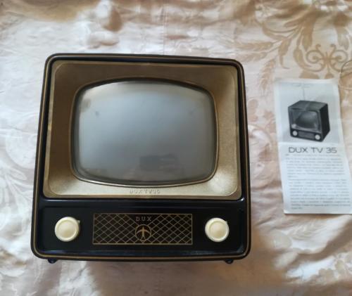 Veduta del Dux Tv in ottimo stato, completo e funzionante. con libretto di istruzioni accanto.